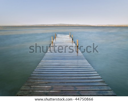 Wooden jetty in a lake. Long time exposure used to create a silk effect on the water surface - stock photo