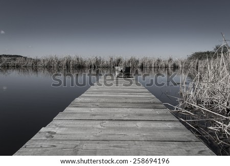 Wooden Jetty in a small lake - stock photo