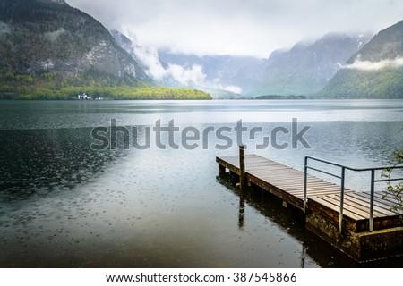 Wooden jetty in Hallstatt lake on a foggy and rainy day - stock photo