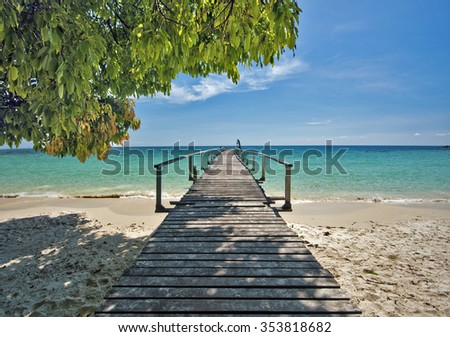 Wooden jetty in tropical beach of Ko Samet island, the shadow from the coastline tree is at foreground, Thailand - stock photo