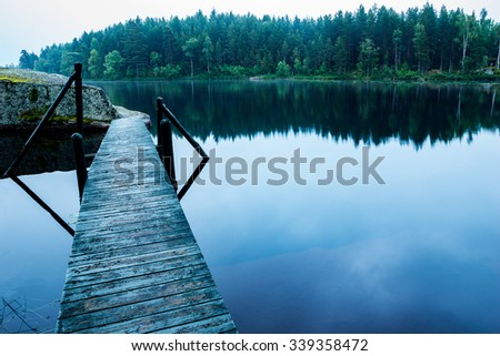 wooden Jetty leading out to rock in forest lake  - stock photo
