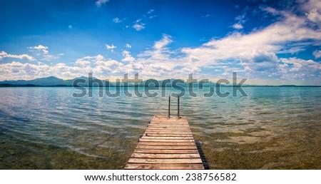 wooden jetty on lake chiemsee panorama  - stock photo