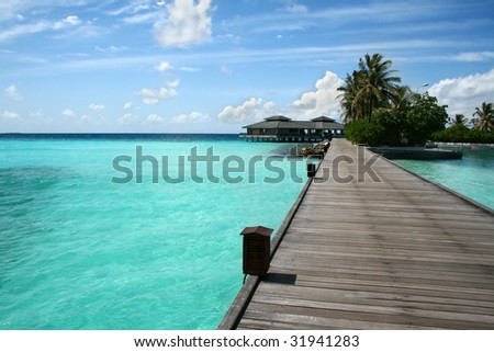 Wooden jetty on over the beautiful Maldivian beach - stock photo