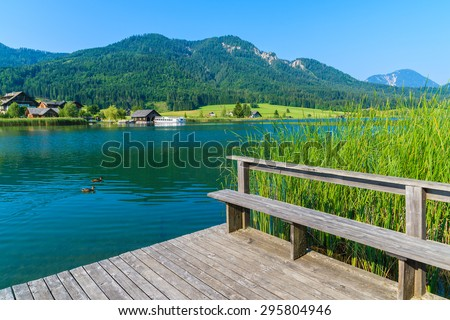 Wooden jetty on shore of Weissensee alpine lake in summer landscape of Alps Mountains, Austria - stock photo