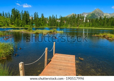 Wooden jetty on Strbske lake in summer, Tatra Mountains, Slovakia - stock photo