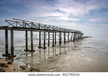 Wooden jetty on the low tide beach