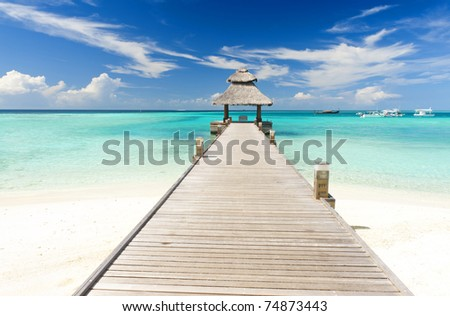 Wooden jetty over the beautiful Maldivian sea with blue sky
