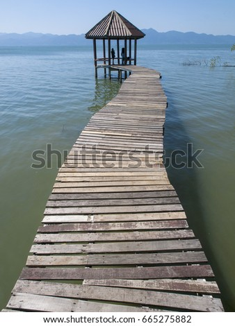 Wooden jetty over the ocean leading to a gazebo at Black Sand Beach eco-walk, near Trat, east Thailand