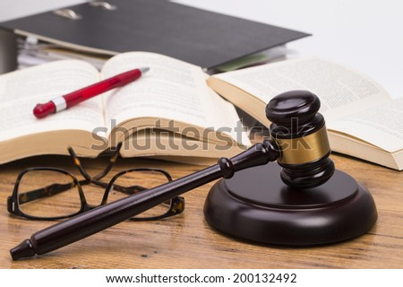Wooden judge gavel and books on a wooden table - stock photo