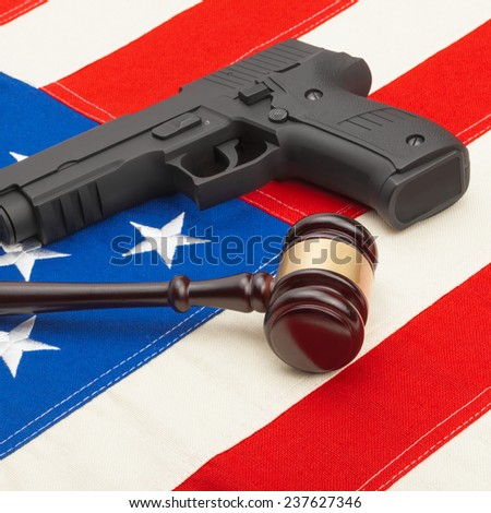 Wooden judge gavel and gun over USA flag - self-defense law concept - stock photo