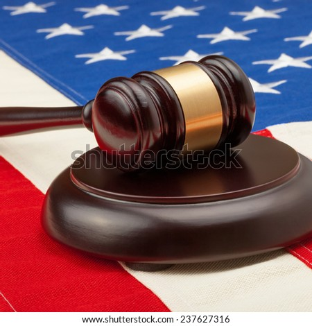 Wooden judge gavel and soundboard laying over USA flag - court judgment concept - stock photo