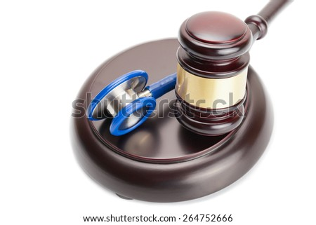 Wooden judge gavel and stethoscope near it - stock photo