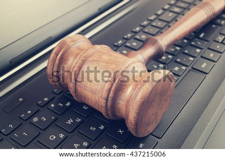 Wooden judge gavel on a laptop computer, cyber law or crime concept