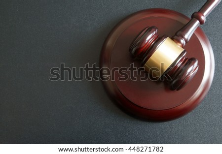 Wooden judge gavel on dark table, legal and law concept with room for text
