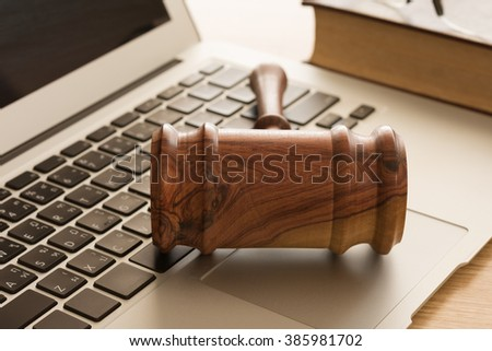 Wooden judge gavel on keyboard laptop computer. Concept of cyber law or law about computer. - stock photo