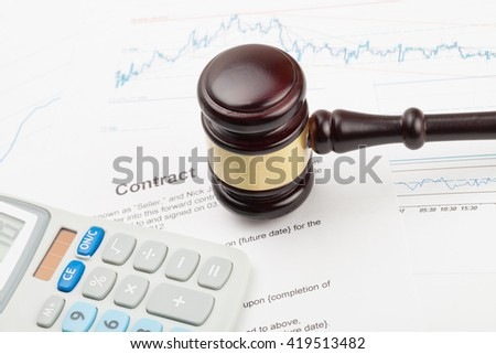 Wooden judge's gavel and calculator above contract over - close up studio shot - stock photo