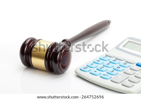 Wooden judge's gavel and calculator close to it - stock photo