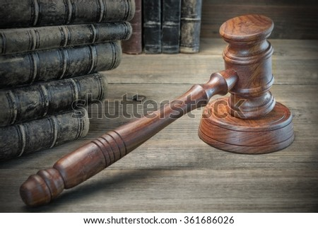 Wooden Judges Gavel And Old Law Books On The Rough Wooden Table In The Background. Law Concept. Front View - stock photo