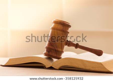 wooden judges gavel resting on top of the legal books. soft focus. - stock photo
