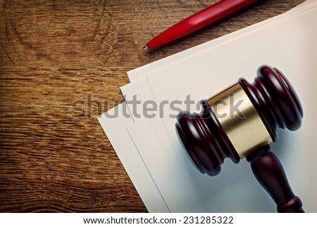 Wooden judges or auctioneers gavel and blank white paper lying on a wooden desk with a ballpoint pen in a concept of judgements or auction knock down, with copyspace - stock photo