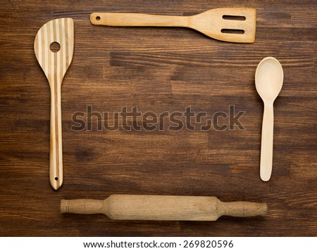 Wooden kitchen tools on vintage wooden background. Top view. - stock photo