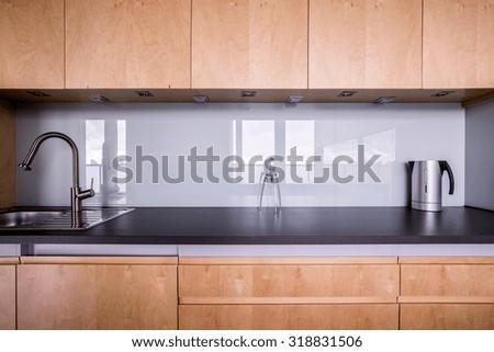 Wooden kitchen unit in stylish contemporary interior - stock photo