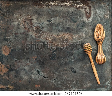 Wooden kitchen utensils on rusted metal plate background. Vintage cooking tools concept - stock photo