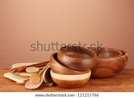 Wooden kitchen utensils on table on brown background