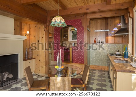 Wooden kitchen with seating arrangement in amazing house with fire place and unique nook. - stock photo