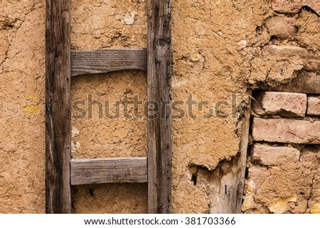 Wooden ladder against old broken brick and dirt wall  - stock photo