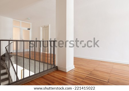 Wooden landing a flight of interior stairs in a fresh white painted building interior with a simple metal railing - stock photo