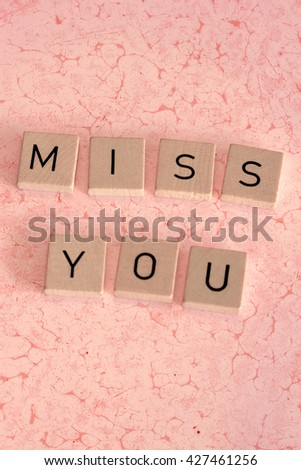 Wooden letters on marbled background - MISS YOU