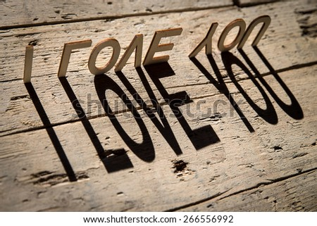 wooden letters on old aged wooden table build the shadow word i love you, vintage style - stock photo