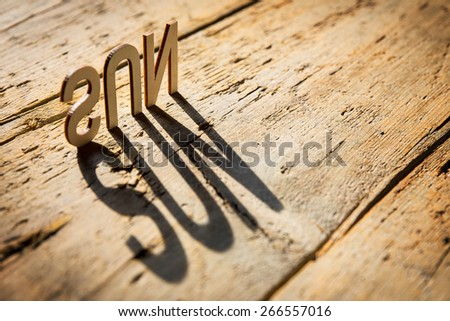 wooden letters on old aged wooden table build the shadow word sun, vintage style - stock photo