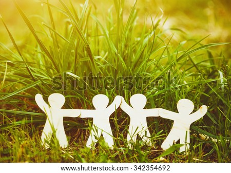 Wooden little men holding hands in summer grass. Symbol of friendship, family, teamwork or ecology concept - stock photo