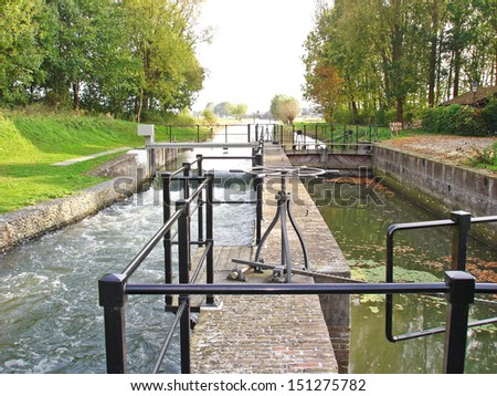 Wooden lock gates and channels of water dam in river Rhine - stock photo