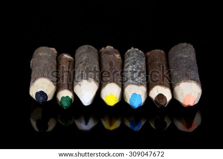 Wooden log colored pencils made of branches - isolated on a black background - stock photo