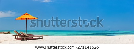 Wooden lounge chairs and orange sun umbrella on a beautiful tropical beach at Maldives