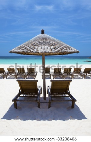 Wooden lounge / deck chairs and umbrella on paradise beach looking out to ocean, blue sky. - stock photo