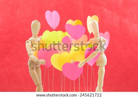 Wooden, male, female, are embracing the heart of all colors, background colors, red - stock photo