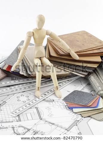 Wooden man, color samples of architectural materials - plastics,  metric folding ruler and architectural drawings of the modern house - stock photo