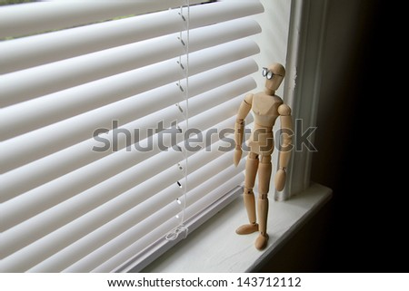 Wooden man looking through window blinds on an overcast day. - stock photo