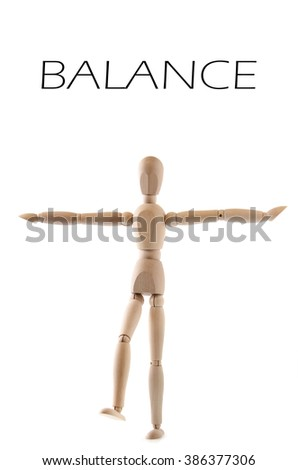 Wooden man or woman is balancing on one foot, isolated on white.