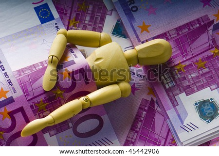 wooden man sleeps under a money - stock photo