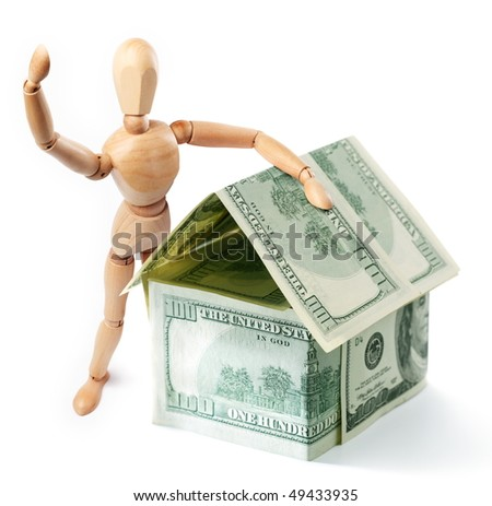 Wooden man standing next to a dollar house - stock photo