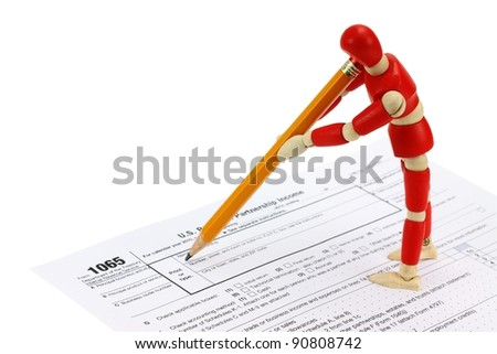 Wooden mannequin completing the 1065 Tax form for LLC's - stock photo
