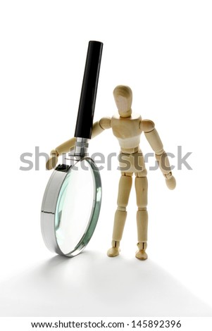 Wooden mannequin holding magnifying glass - stock photo