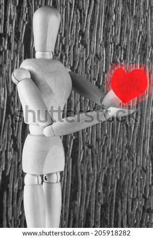 Wooden mannequin holding red heart - stock photo