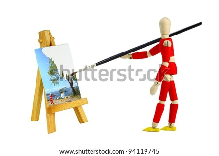 Wooden mannequin with an easel painting a landscape isolated on white - stock photo