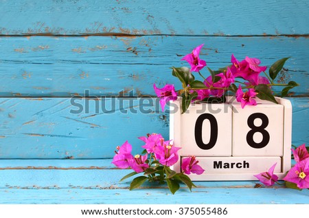 wooden March 8 calendar, next to purple flowers on old blue rustic table. selective focus  - stock photo